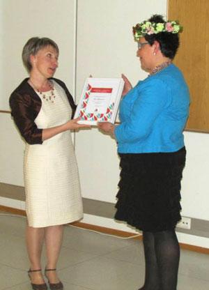 Puheenjohtaja Anne Auramo onnittelee Eija Ahvenjärveä